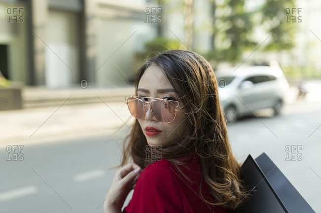 Close-up of confident woman wearing sunglasses carrying shopping bag on street in city