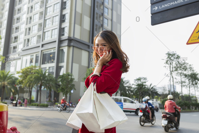 Smiling woman carrying shopping bags talking over smart phone while standing on street