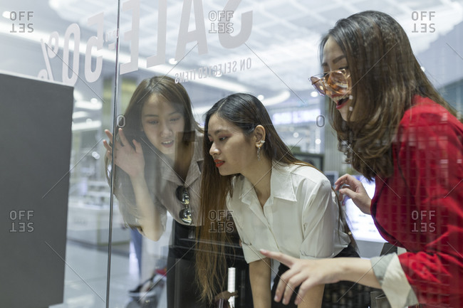 Curious female friends doing window shopping seen through glass in mall