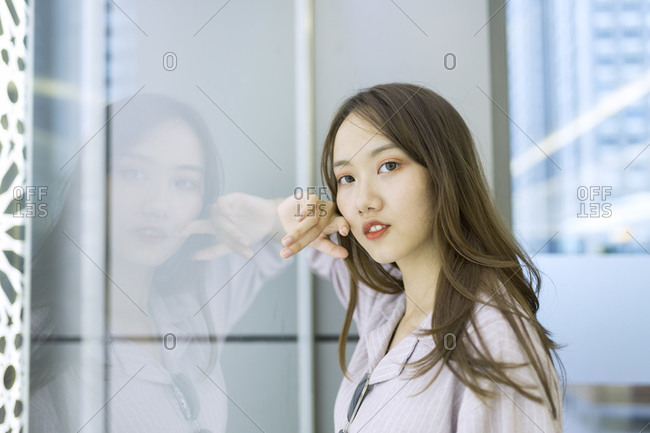 Close-up of young woman standing by window in shopping mall