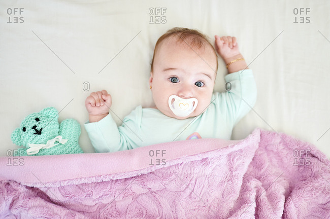 Portrait of baby girl with pacifier and cuddly toy lying on bed