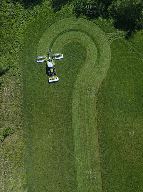 Russia- Moscow Oblast- Aerial view of tractor mowing green field