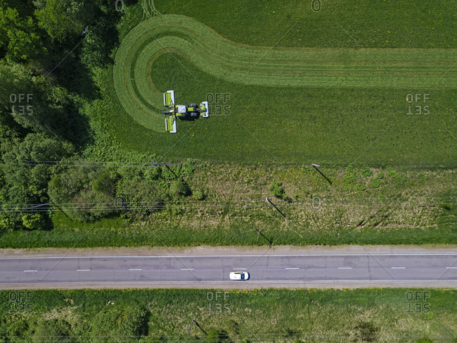 Russia- Moscow Oblast- Aerial view of car driving along country road past tractor mowing green field