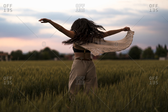 Woman dancing at field in the evening light