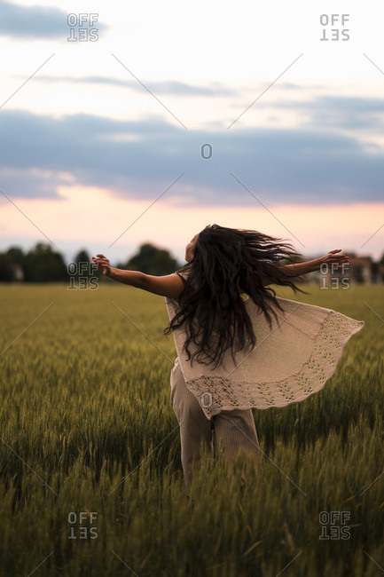 Woman dancing on field in the evening light