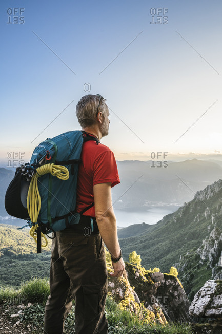 Hiker with backpack looking at mountains against clear sky during sunset- Orobie- Lecco- Italy