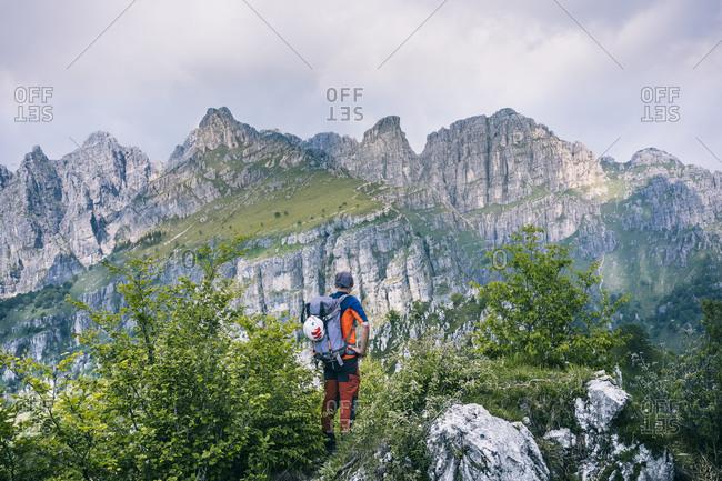 Hiker standing on mountain path enjoying view- Orobie- European Alps- Como- Italy