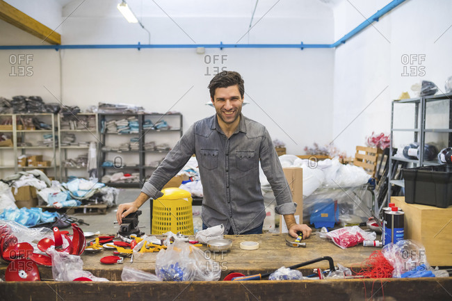 Portrait of smiling man at workbench with fencing supplies