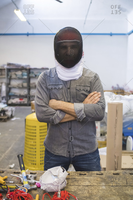Man wearing fencing mask in a workshop