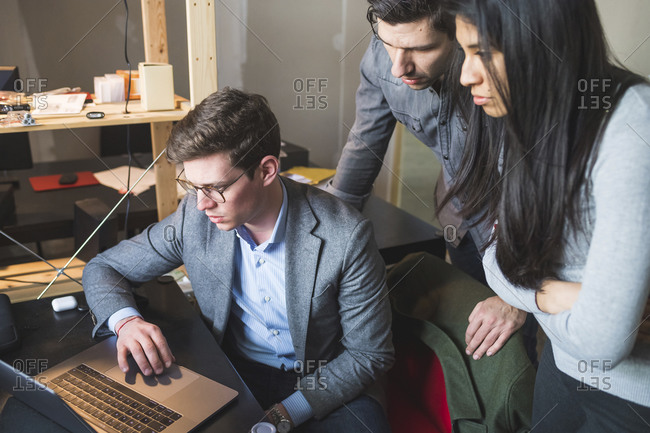 Three business people sharing laptop at desk in office