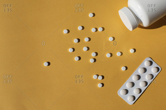 Scattered white pills against a yellow background
