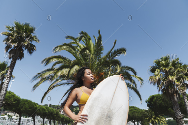 Female surfer with surfboard outdoors