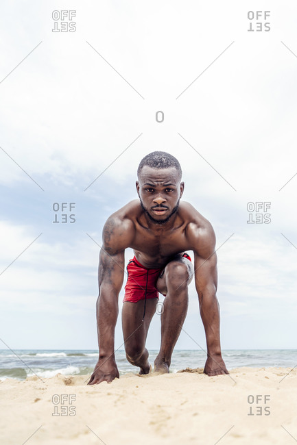 Athletic man in start position on beach