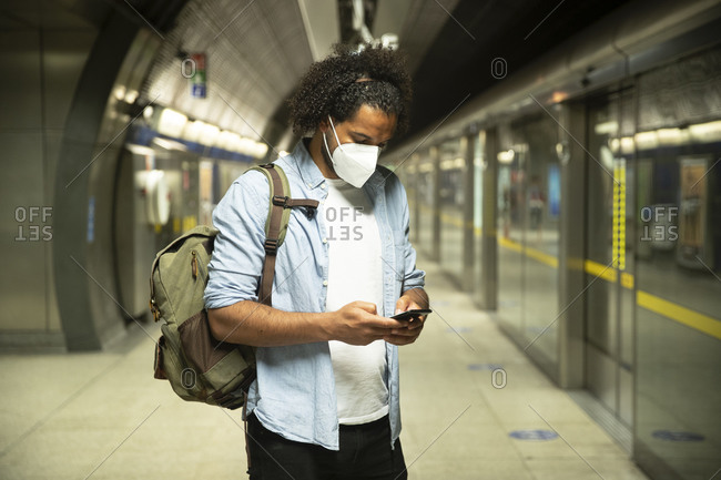 Young man wearing protective mask standing at underground station platform- London- UK