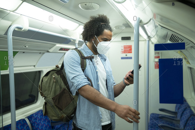 Man wearing protective mask standing in underground train looking at cell phone- London- UK