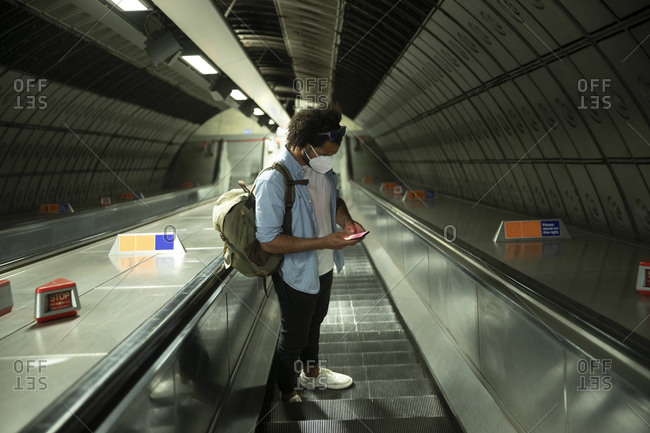 Man wearing protective mask standing on escalator looking at mobile phone- London- UK