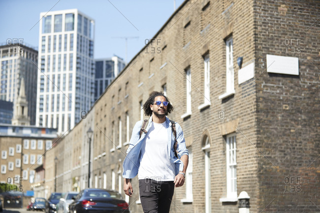 Portrait of young man with backpack walking on residential street- London- UK