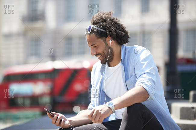 Portrait of smiling young man sitting outdoors listening music with cell phone and earphones- London- UK