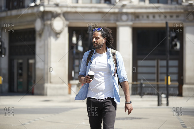 Portrait of young man with coffee to go crossing the street while listening music with earphones- London- UK