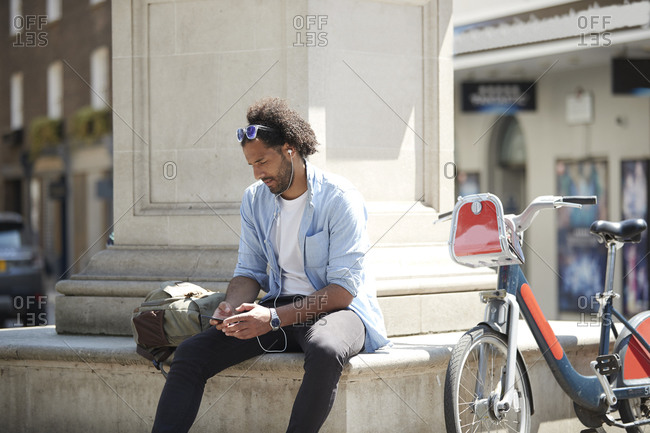 Young man with rental bike listening music with cell phone and earphones in the city- London- UK