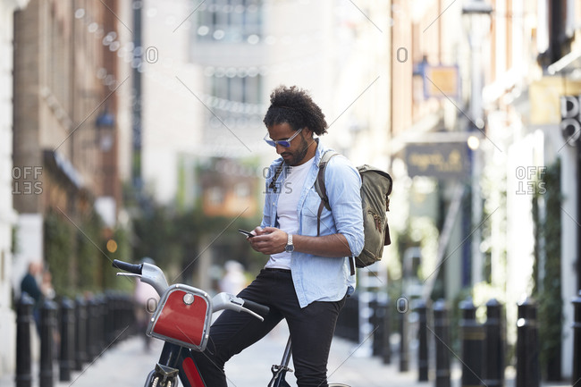 Young man with rental bike and backpack using cell phone in the city- London- UK