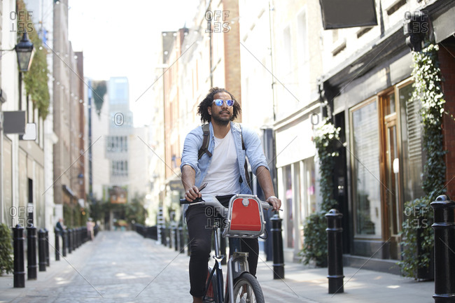 Portrait of young man riding on rental bike in the city- London- UK