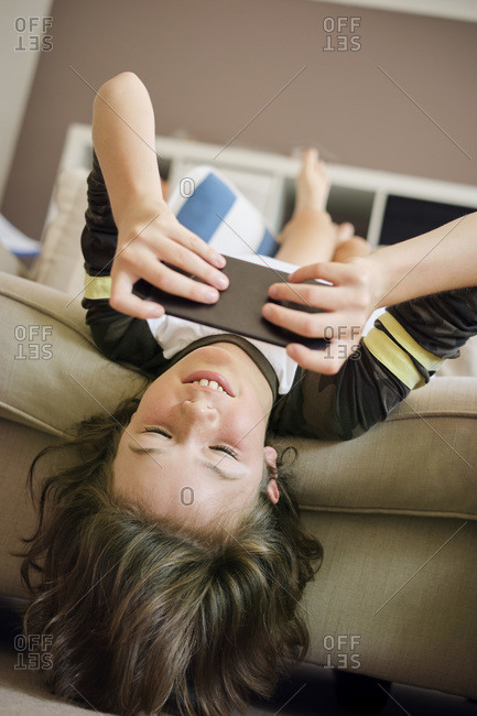 Boy playing games on smart phone while sitting on sofa at home