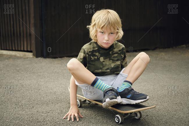 Cute boy sitting on skateboard at yard