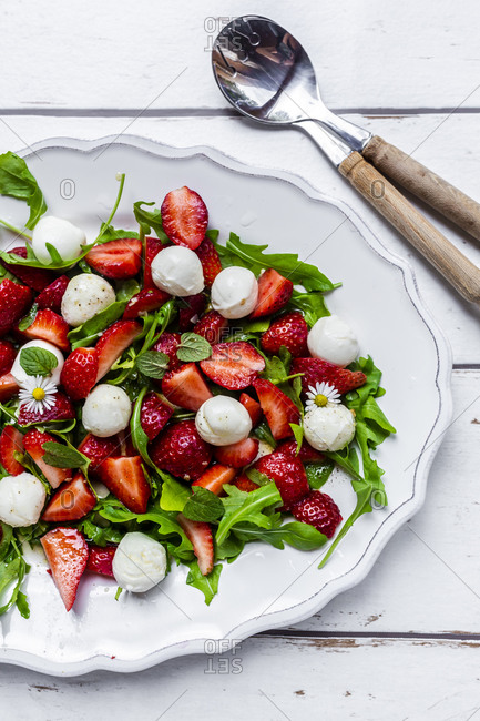 Plate of vegetarian summer salad with arugula- strawberries- mozzarella- mint and daisies