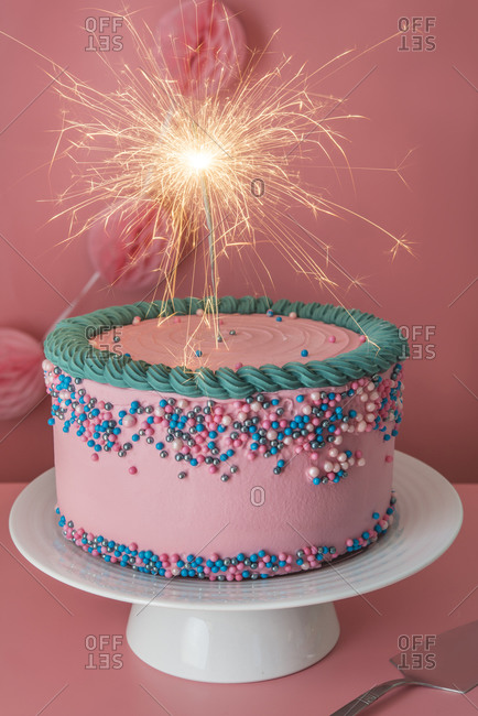 Cake stand with strawberry birthday cake decorated with burning sparkler