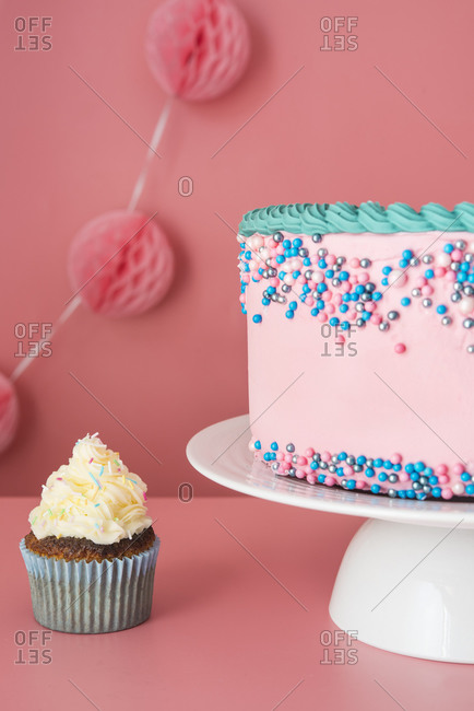Cake stand with strawberry birthday cake and single cupcake