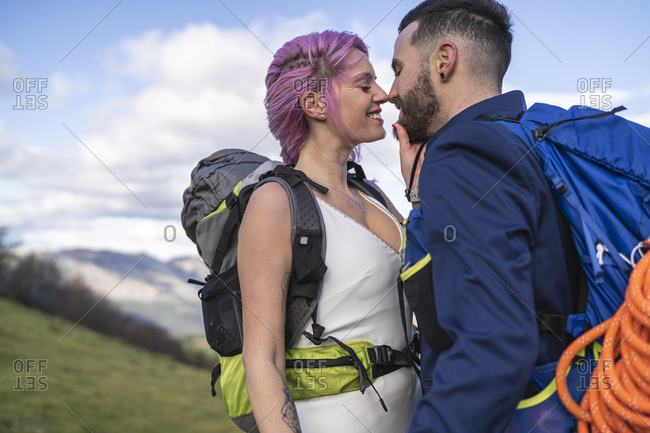 Kissing bridal couple with climbing backpacks at Urkiola mountain- Spain