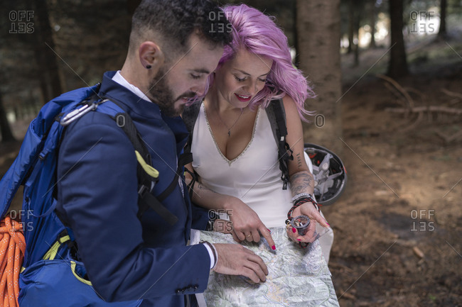 Bridal couple with hiking map in the woods