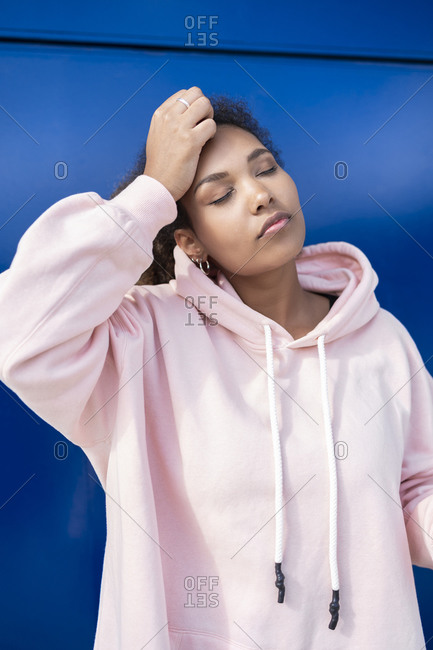 Young woman with closed eyes wearing pink hoodie sweater in front of blue wall