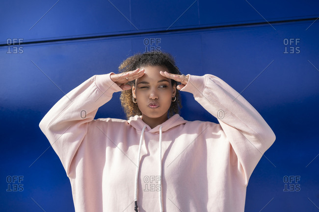 Young woman looking out wearing pink hoodie sweater in front of blue wall