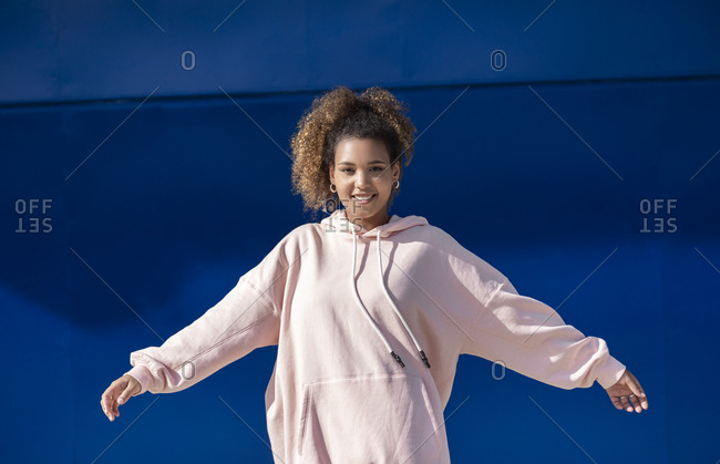 Smiling young woman wearing pink hoodie sweater in front of blue wall