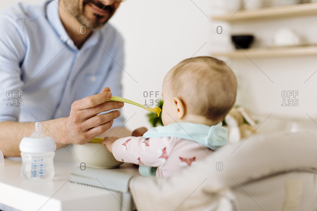 Father feeding baby girl in high chair