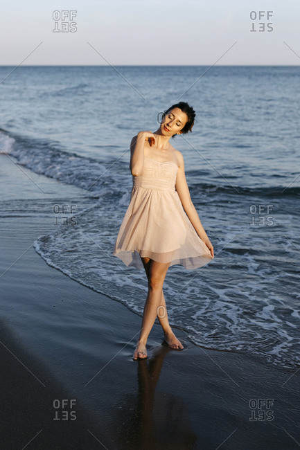 Delicate ballerina dancing on the beach at sunset