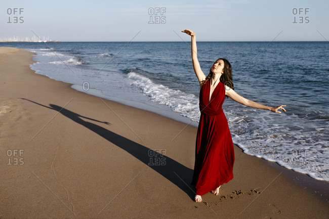 Delicate woman in red dress dancing at the sea- feeling the sun