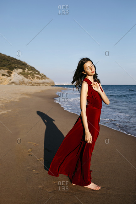 Delicate woman in red dress standing at the sea- feeling the sun