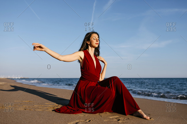 Delicate woman in red dress sitting on the beach- feeling the sun