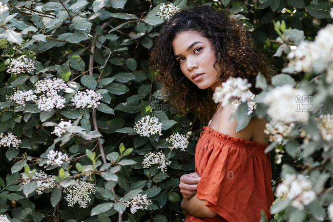 Beautiful woman standing in nature between flowers
