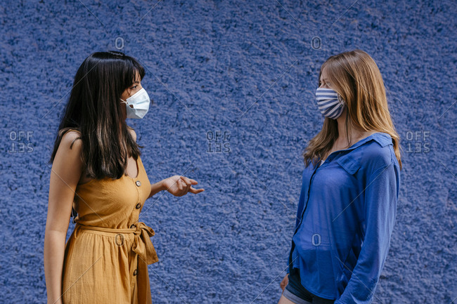 Female friends wearing masks talking while maintaining distance against blue wall in city
