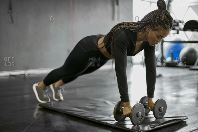 Female athlete with braided hair holding dumbbells while exercising on mat in gym