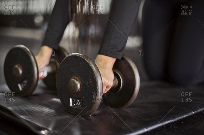 Close-up of young woman holding dumbbells on mat in gym