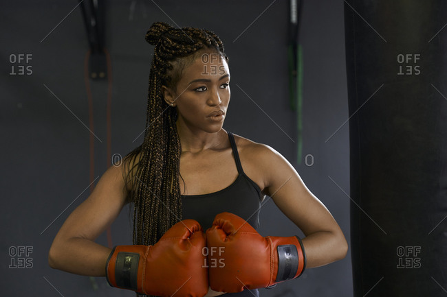 Young woman with braided hair wearing red boxing gloves in gym