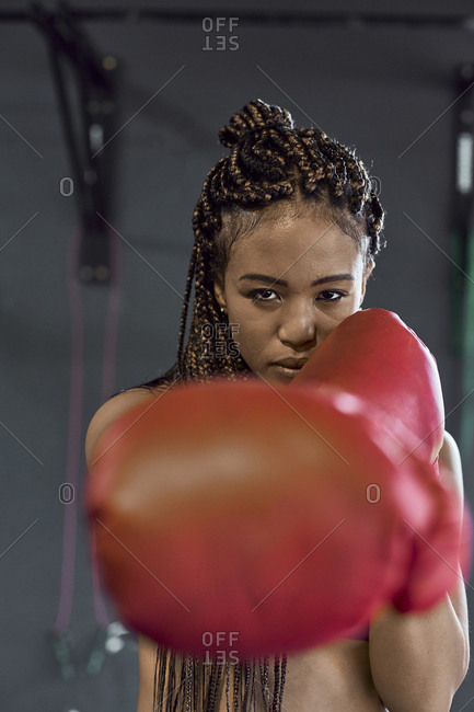 Confident young woman wearing red boxing gloves exercising in gym