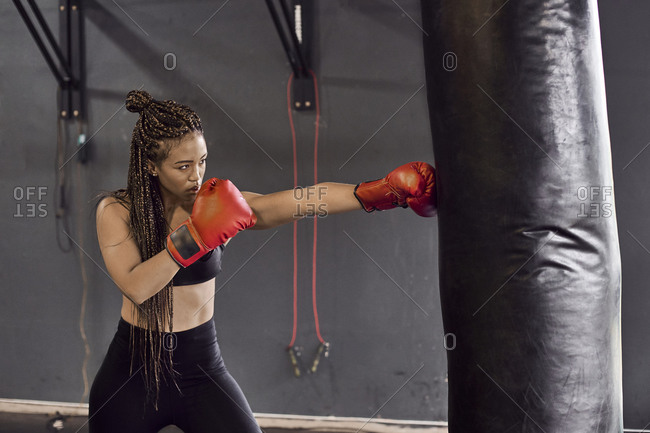 Female boxer wearing red gloves practicing boxing drill on punching bag in gym