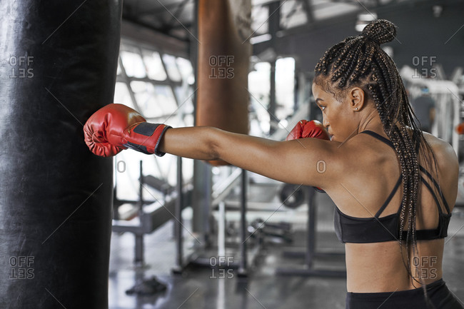 Female athlete wearing red gloves practicing boxing drill on punching bag in gym