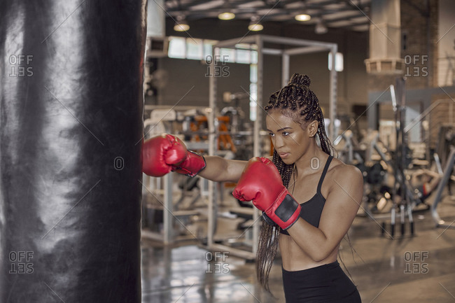 Young woman wearing red gloves practicing boxing drill on punching bag in gym